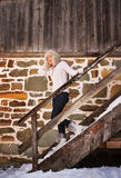 Cheerful woman in white sweater on stairs of cosy mountain house Royalty Free Stock Photo