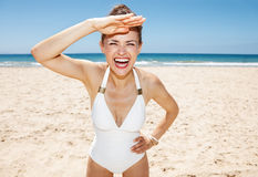 Cheerful woman in white swimsuit at sandy beach on sunny day Royalty Free Stock Photo