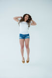 Cheerful woman in white t-shirt and hot pants jumping Stock Photos