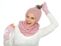 Cheerful woman in winter clothing holding pompom Royalty Free Stock Image
