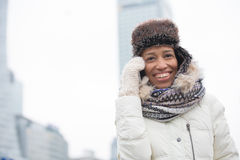 Cheerful woman in winter wear using cell phone outdoors Royalty Free Stock Photos