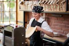Cheerful woman working with pasta machine Royalty Free Stock Photography