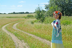 The cheerful woman with a wreath on the head goes on a path in t Stock Image