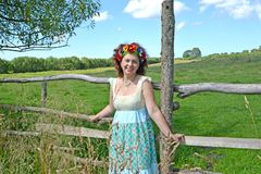The cheerful woman with a wreath on the head stands near a fence Stock Images