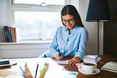 Cheerful woman writing checks at desk Stock Photography