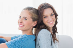 Cheerful women back against back and looking at camera Royalty Free Stock Images
