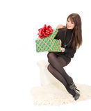 Cheerful women with a big box present. Cheerful woman with a big box present sitiing on the ottoman Royalty Free Stock Photos
