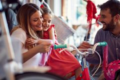 Cheerful woman buying new bicycle and helmet for girl in bike shop. Cheerful women buying new bicycle and helmet for cute girl in bike shop royalty free stock photo