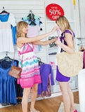 Cheerful women choosing clothes together Stock Images