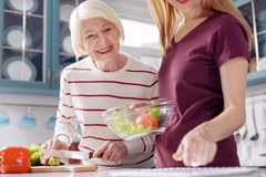 Cheerful women consulting tablet for salad recipe. Helpful technology. Charming young women and her elderly mother making a vegetable salad and checking the Stock Image