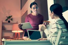Cheerful women discussing project in non-formal ambience. Informal ambience. Two charming female colleagues eating pizza and drinking tea while discussing their Stock Photography