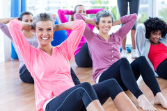 Cheerful women doing sit ups on hardwood floor Royalty Free Stock Photos