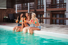 Cheerful women drinking cocktails and laughing near swimming pool Stock Photo