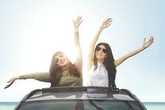 Cheerful women enjoying freedom on car sunroof. Young cheerful women wearing sunglasses, enjoying freedom on a car sunroof on the beach Stock Image