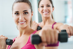 Cheerful women exercising at the gym. Cheerful young women exercising at the gym and weightlifting using dumbbells, they are smiling at camera Royalty Free Stock Images