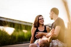 Man and woman having funny conversation. Cheerful women gazing at her men outside Stock Photos