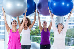 Cheerful women holding exercise balls with arms raised Stock Images