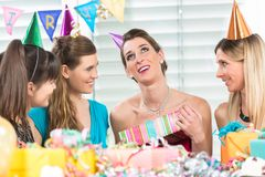 Cheerful woman holding a gift box during a surprise birthday party. Cheerful women holding a gift box while looking up overwhelmed by the appreciation of her stock image
