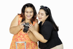 Cheerful women looking at digital camera. Two cheerful women looking their photo at digital camera, isolated on white background Stock Images
