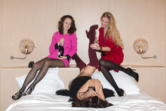 Cheerful women lying and drinking champagne Royalty Free Stock Photography
