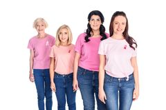 Women in pink t-shirts with ribbons. Cheerful women in pink t-shirts with ribbons smiling at camera isolated on white Stock Photos