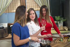Cheerful women preparing food and having fun in kitchen. Stock Photography