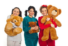 Cheerful women in pyjamas with teddy bears. Three women in pyjamas holding teddy bears and smiling isolated on white background Stock Photos