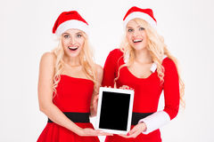 Cheerful women in santa cloth showing tablet computer screen Royalty Free Stock Photo