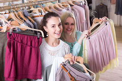 Cheerful women selecting new garments Royalty Free Stock Photos