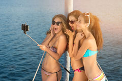 Cheerful women with selfie stick. Girls taking selfies on yacht. Young models on vacation. Happy youth on a trip Royalty Free Stock Photo