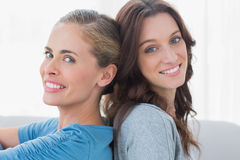 Cheerful women sitting back against back Stock Image