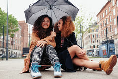 Cheerful women sitting on skateboard with umbrella Royalty Free Stock Images