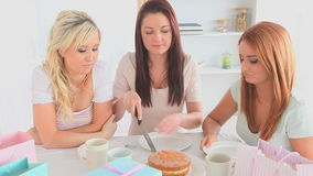 Cheerful women sitting at a table eating cake stock video footage