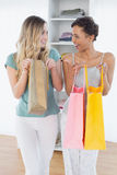 Cheerful women standing with shopping bags at home Royalty Free Stock Photos