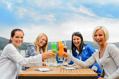 Women toasting cocktails outdoor restaurant terrace. Cheerful women toasting with cocktails at outdoor restaurant summer terrace Royalty Free Stock Photos