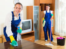 Cheerful women in uniform doing housework. In the living-room Stock Photo