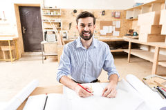 Cheerful wood master with beard making drafts at workplace Stock Images