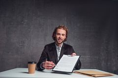 Cheerful worker giving treaty for signing it. Portrait of happy bearded employer showing contract while sitting at table. Append signature concept Royalty Free Stock Photography