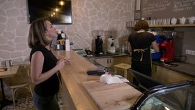 Cheerful worker serving female customers who use their smartphone app and bitcoin crypto currency to pay in a coffee shop -. Cheerful worker serving female stock footage