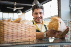 Cheerful worker standing and presenting a bread Royalty Free Stock Photography