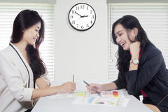 Cheerful workers with financial chart on desk Royalty Free Stock Image