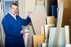 Cheerful workman standing with plywood pieces. In picture framing workshop Stock Image