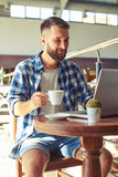 Cheerful young adult man drinking coffee Royalty Free Stock Photography