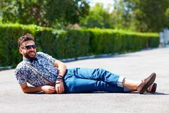 Cheerful young adult man lying on the road Royalty Free Stock Photography