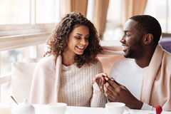 Cheerful young African American couple getting engaged in the caf. Happiest women in the world. Smiling cheerful positive African American couple sitting in the Royalty Free Stock Image