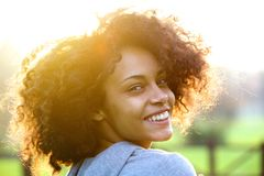 Cheerful young african american woman smiling outdoors stock photo