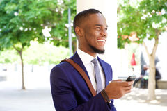 Cheerful young african businessman with cell phone Royalty Free Stock Images