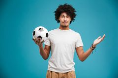 Cheerful young african curly man football player. Image of cheerful young african curly man football player standing isolated over blue background holding ball Stock Image