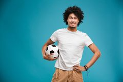 Cheerful young african curly man football player. Image of cheerful young african curly man football player standing isolated over blue background holding ball Royalty Free Stock Image