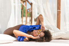 Cheerful young african lady taking tan on beach stock photo